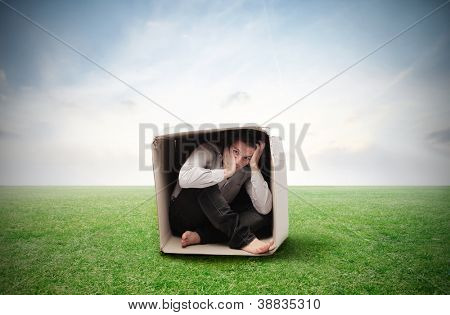 Man crouched in a box in a large grace field