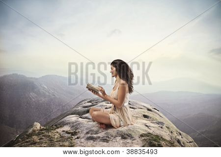 Brown girl reading a book on the top of a mountain
