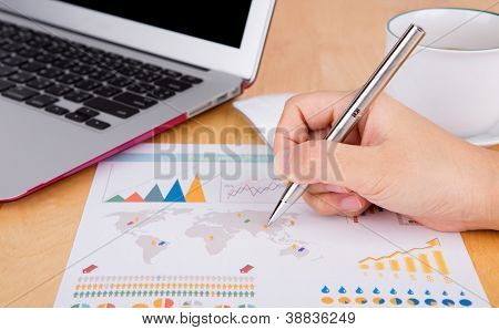 Hand write on financial chart on the table with laptop and coffee