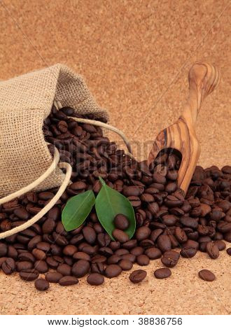 Coffee beans in a hessian drawstring sack and loose with leaf sprigs over cork background.