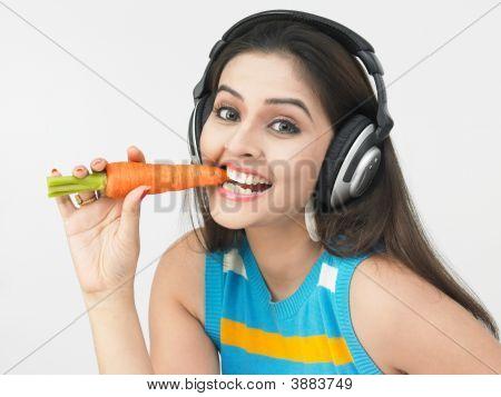 Young Asian Woman Of Indian Origin Eating A Carrot