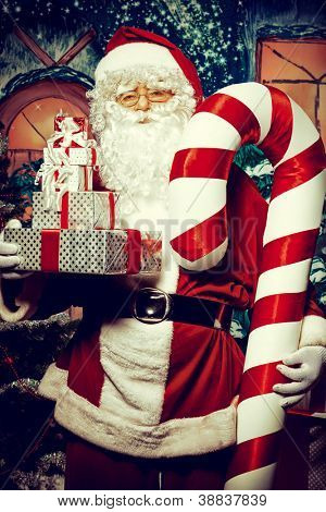 Santa Claus posing with presents over Christmas background.