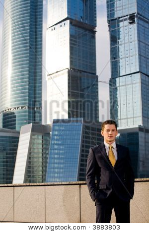 Friendly Young Businessman Standing Against Skyscraper
