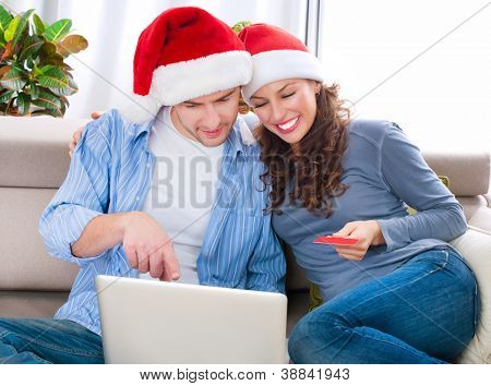 Christmas Online Shopping. Happy Smiling Couple Using Credit Card to Internet Shop. Young couple with laptop and credit card buying online. Christmas and New Year Gifts. e-shopping