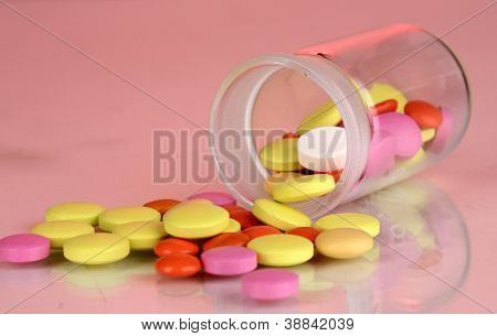 Pills in receptacle on red background