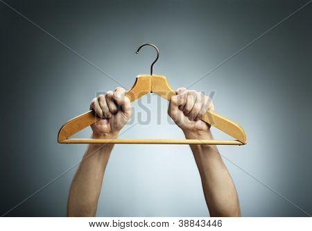 Man holding an old wooden clothes hanger in his hands.