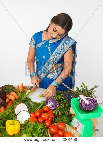 Woman Cutting Vegetables And Talking In The Phone