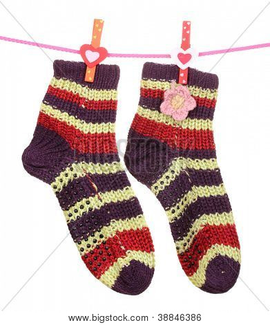 Pair of knit striped socks hanging on a rope isolated on white
