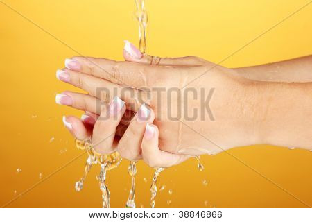 Washing woman's hands on orange background close-up