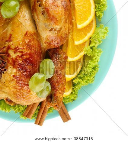 whole roasted chicken with lettuce, grapes, oranges and spices on blue plate on white background close-up