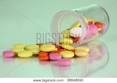 Pills in receptacle on green background
