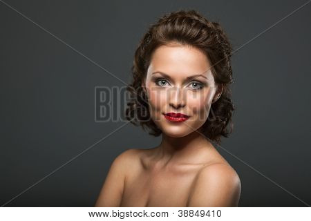Face of a beautiful young brunette woman with bright makeup and curly hair