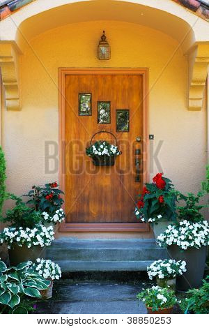 Weathered wood stained home door with three windows and flowers