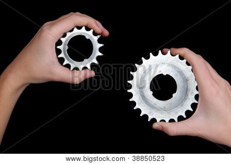 Man holding a pair of old metallic cogwheels in his hands