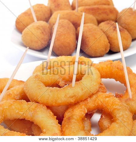 some plates with spanish calamares a la romana, squid rings breaded and fried, and croquettes served as tapas