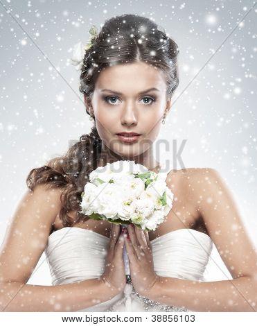 Novia joven atractiva con el ramo de rosas blancas sobre fondo Nevado de Navidad