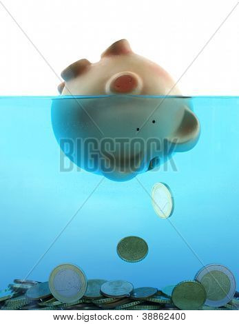 Drowning in debt represented by a piggy bank sinking in blue water