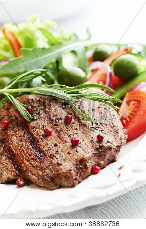 Grilled beef steak with salad on a plate
