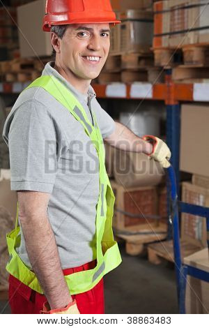 Portrait of happy mid adult foreman holding handtruck at warehouse