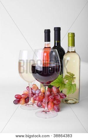copo de vinho, garrafas de vinho e uvas