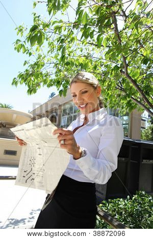 A pretty blonde business woman reading a newspaper