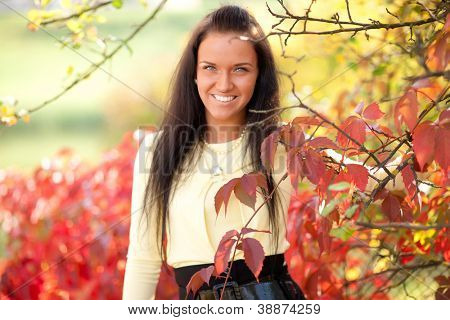 Beautiful young girl with red  autumn maple leaves