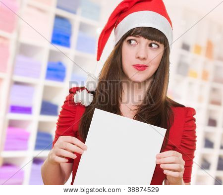 worried christmas woman holding a blank card in a shop
