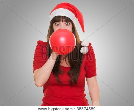 woman blowing balloon and wearing a christmas hat against a grey background