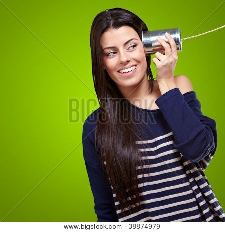 Female Holding A Metal Tin As A Telephone On A Green Background