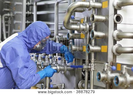 Technician in blue,protective uniform,mask and goggles fixing valves in plant