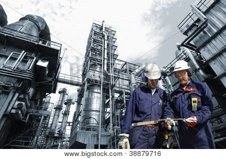 refinery engineers with large industry in background