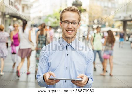 Young businessman using tablet computer in public space, group of people
