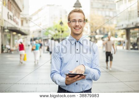 Young businessman with glasses and tablet computer on street