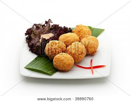 Deep Fried Rice Croquette with Salmon and Cream Cheese. Garnished on Green Leaf with Sauce