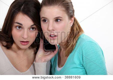 Girls listening to a cellphone