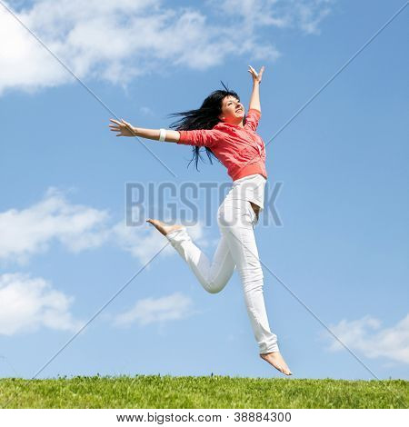pretty young woman jumping on green grass