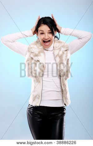 Cute young girl in fur is screaming isolated on a blue