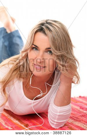 Beautiful Mid aged woman listening music with headphones over a white background