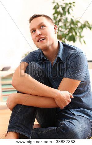 Porträt von schöner junger Mann denken zu Hause auf dem Boden