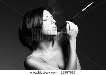 Black and white erotic portrait of sexy woman smoking in studio