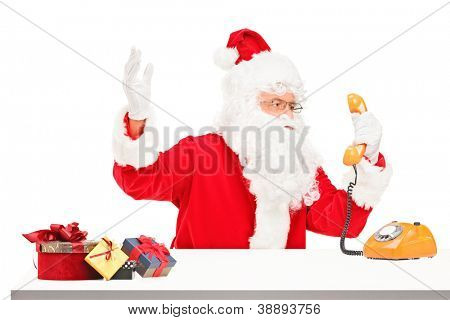 Nervous Santa Claus screaming on a telephone isolated on white background