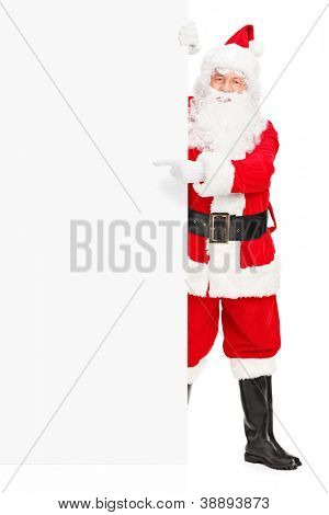 Full length portrait of a Santa claus posing next to a blank billboard and pointing isolated on white background