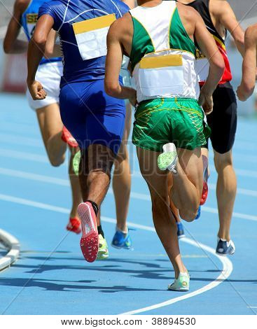 Athletes from back running on track during a competition