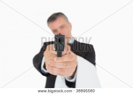 Waiter in suit holding black gun directly ahead