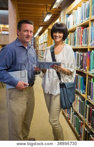 Man holding book standing next to woman using tablet pc in the library