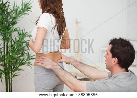 Doctor sitting while examining the hips of a woman in a room