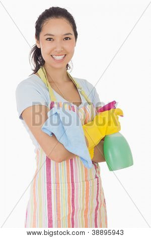 Happy woman holding spray bottle and rag in apron and rubber gloves