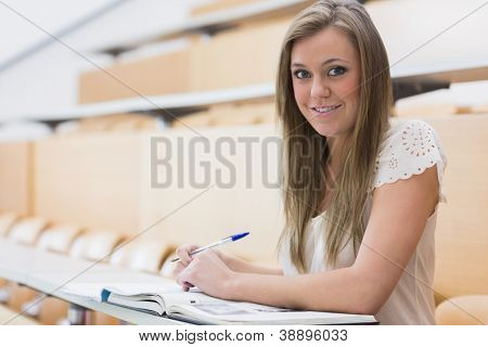Girl sitting while smiling at the lecture hall making notes