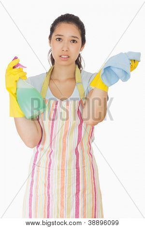 Overworked woman holding rag and spray bottle in apron and rubber gloves