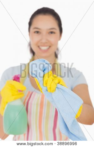 Happy woman cleaning window with cloth and spray bottle